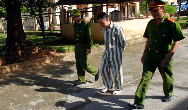 Police escort a man who is being released from Hoang Tien prison, about 100 km (62 miles) outside Hanoi August 30, 2013.