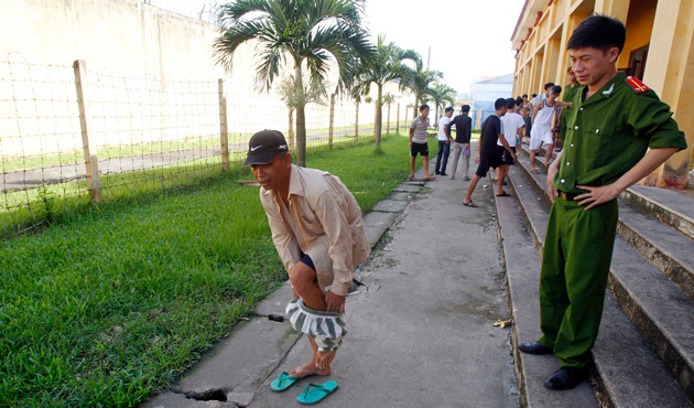 A man takes off his prison uniform while he is being released from Hoang Tien prison, about 100 km (62 miles) outside Hanoi August 30, 2013.