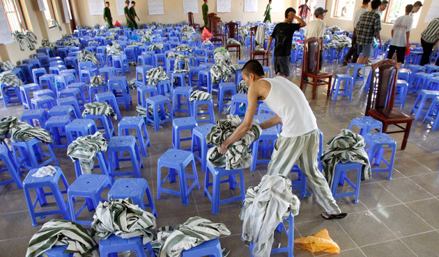 A man leaves his prison uniform on a stool amongst other discarded prison uniforms during his release from Hoang Tien prison, about 100 km (62 miles) outside Hanoi August 30, 2013.