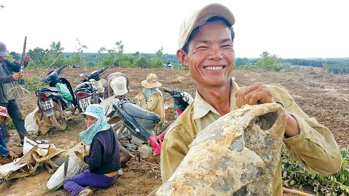 Tran Van Ngac from Tan Hiep village looks happy with a 35kg metal piece in his hands.