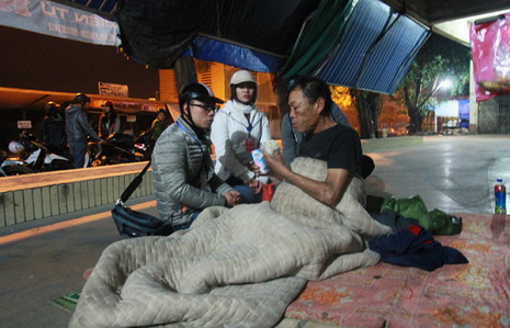 Two members of the Trai Tim Viet (Vietnamese Hearts) Club in northern Vietnam's Hai Phong City are pictured gifting milk and warm clothing to a homeless man on New Year's Eve.