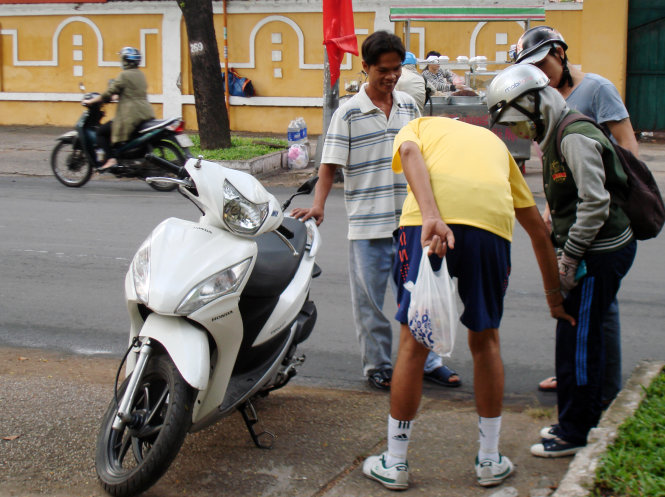 A common sight in HCMC streets unfolds as a young woman's bike fell over on Nam Ky Khoi Nghia street during rush hour, at 7.50 on January 5, 2015. Her bike was immediately taken to the sidewalk and she was surrounded by some caring passengers.