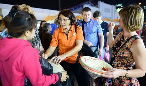 """A group of Ukrainian tourists are seen eagerly choosing among """"non la"""" (Vietnamese conical leaf hat) at Ben Thanh night market in downtown Ho Chi Minh City."""