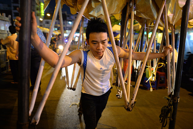 A man is pictured pushing his tent system, with wheels and light bulbs attached, to Ben Thanh night market.