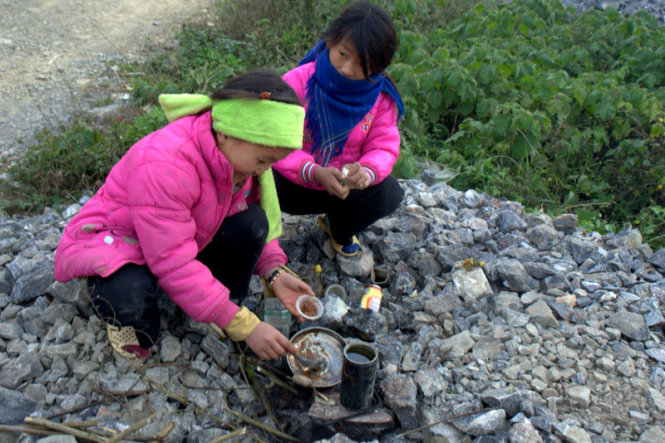 Two girls are seen playing a cooking game on the way to Xin Cai Commune.