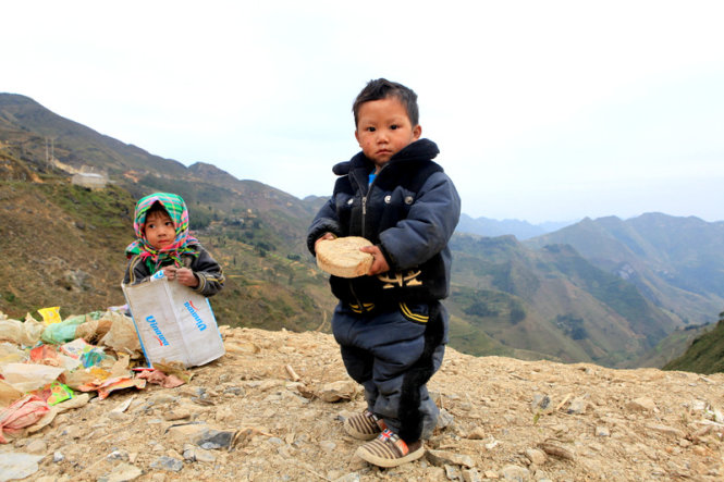 Two little kids are pictured along the way to Xin Cai Commune.