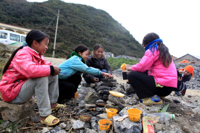 School girls from a school in Xin Cai Commune are pictured enjoying their cooking game in the chilly weather.