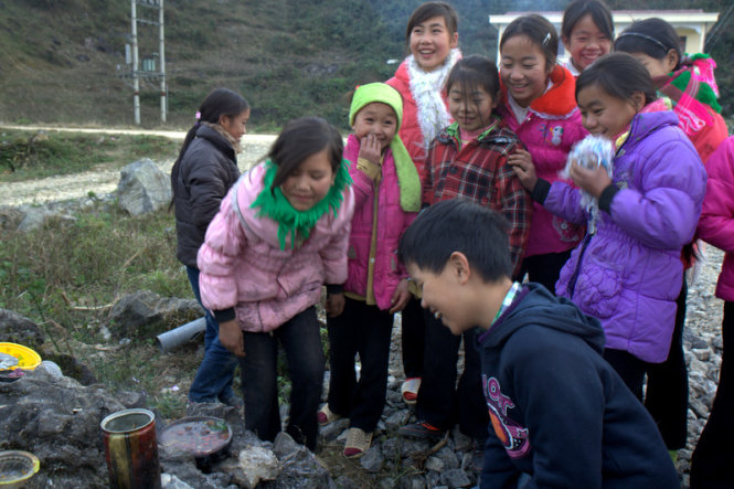 Local kids and teenagers delighted at a dish which they are cooking.