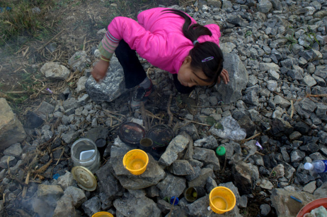 A young girl is seen trying to build a fire.