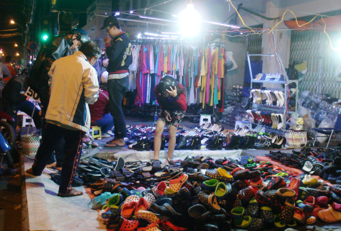 Past 12:00 am on February 11, 2015, the footwear and clothing stalls on District 1's Nguyen Trai Street were still packed with young clients.