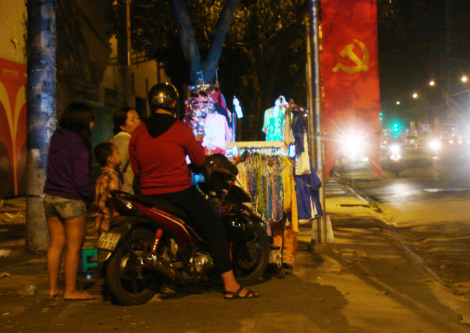 A young couple is pictured picking Tet clothes for their would-be little son at an isolated stall on Binh Thanh District's Phan Dang Luu Street at 11:16 pm on February 11, 2015.
