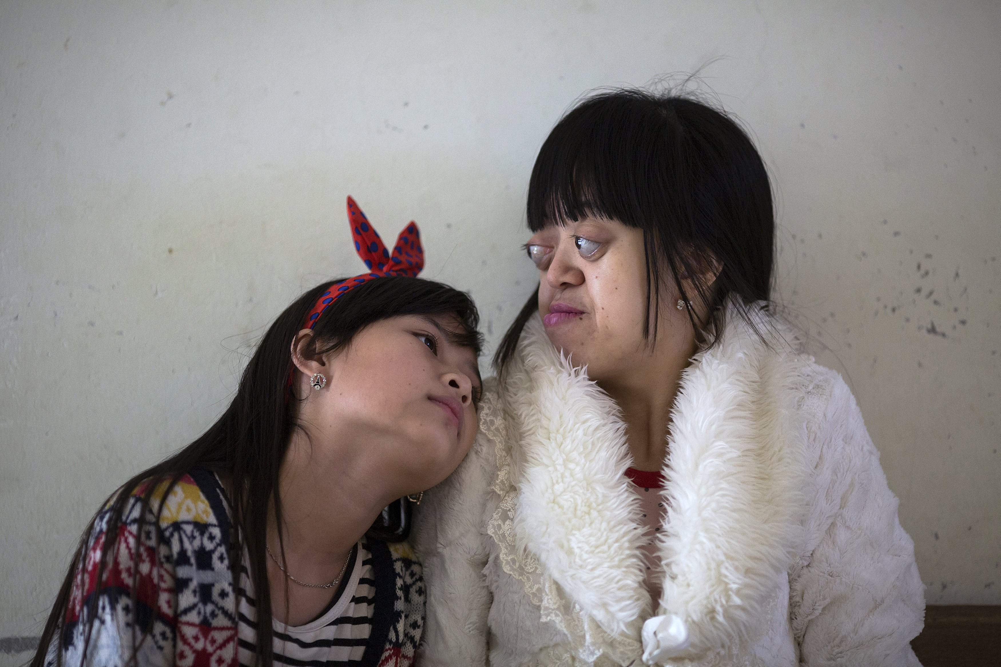 Nguyen Thi Van Long (R) and her best friend Dinh Thi Huong, who is deaf and mute, spend time together at Friendship village, a hospice for Agent Orange victims outside Hanoi April 8, 2015. The fathers of both girls were soldiers who were exposed to the Agent Orange during the Vietnam war and health officials link the girls' health conditions to the defoliant. Some 120 children and 60 Vietnamese veterans stay at Friendship village, which was established in 1998.