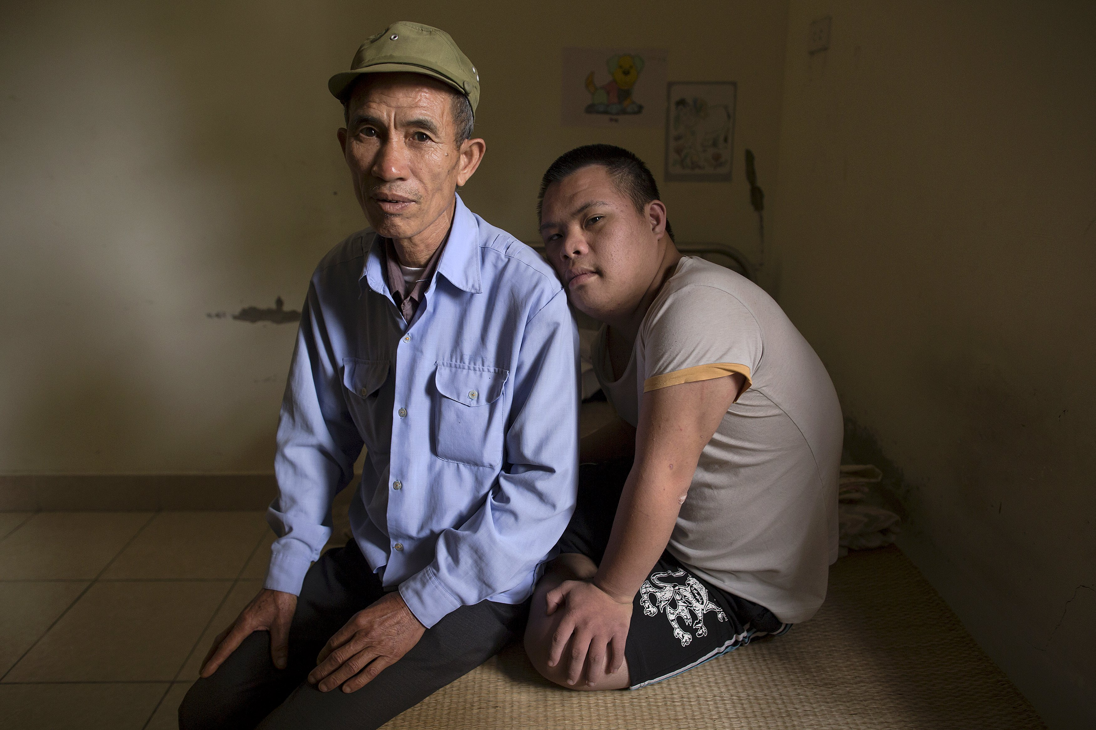 3-year-old former soldier, Nguyen Hong Phuc, sits on the bed with his son Nguyen Dinh Loc, 20, who is recovering from tumour surgery at Friendship village, a hospice for Agent Orange victims, outside Hanoi April 8, 2015. Nguyen Dinh Loc has serious mental and physical problems that his family and doctors link to his father's exposure to Agent Orange. His father joined the military after the U.S. army stopped using Agent Orange in 1971, but lived in areas heavily contaminated by it, including near Danang airport, where the chemical defoliant was stored.