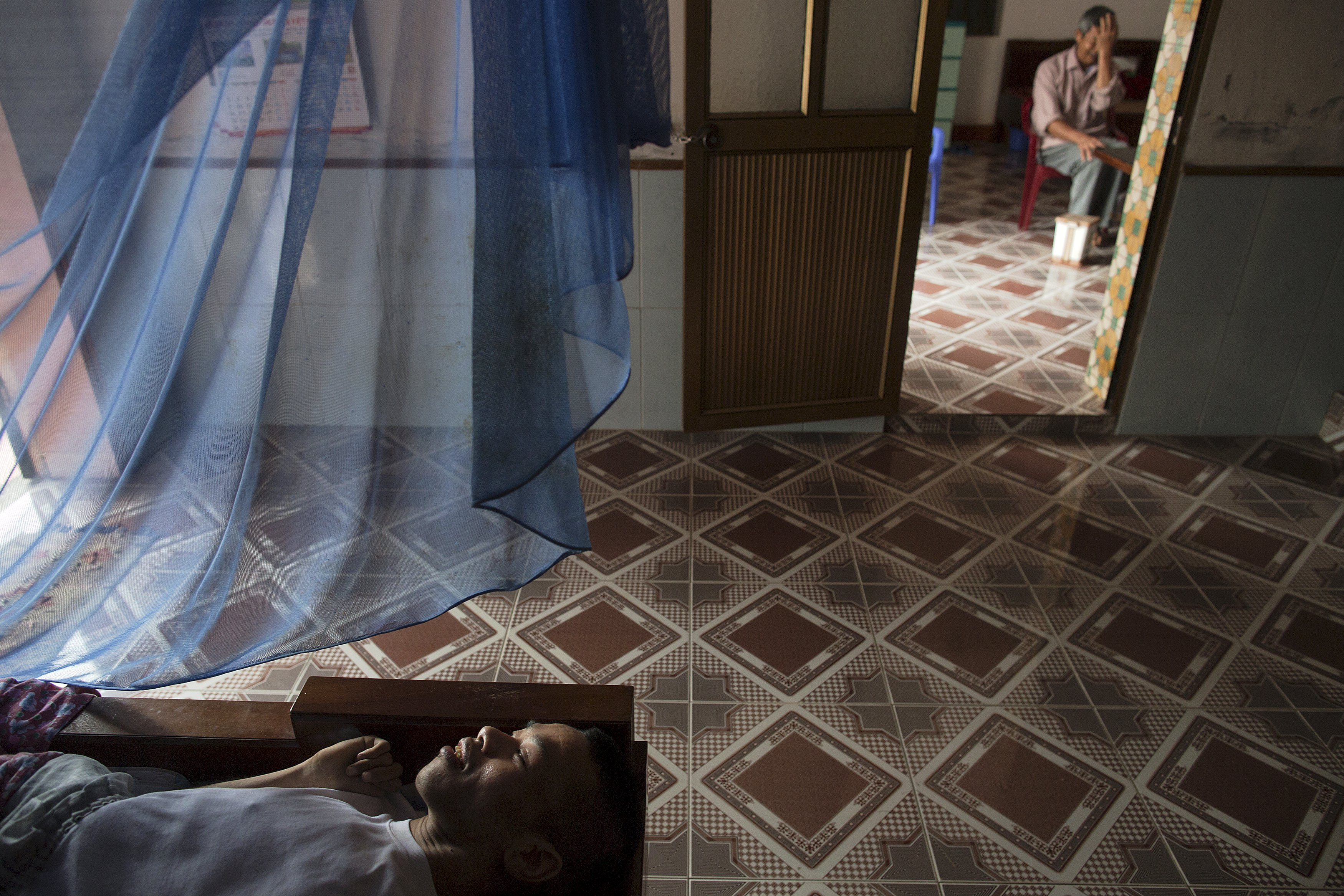 Lai Van Manh rests in bed as his father Lai Van Bien receives guests in their house in Tuong An village, in Thai Binh province in northern Vietnam April 9, 2015. Lai Van Bien, a former intelligence officer in the Vietnamese army in the North, said that during the Vietnam War he served in an area that was heavily contaminated by Agent Orange. Lai Van Bien and his wife now care for their two physically and mentally disabled sons whose health condition the family and local officials link to the effects of Agent Orange.