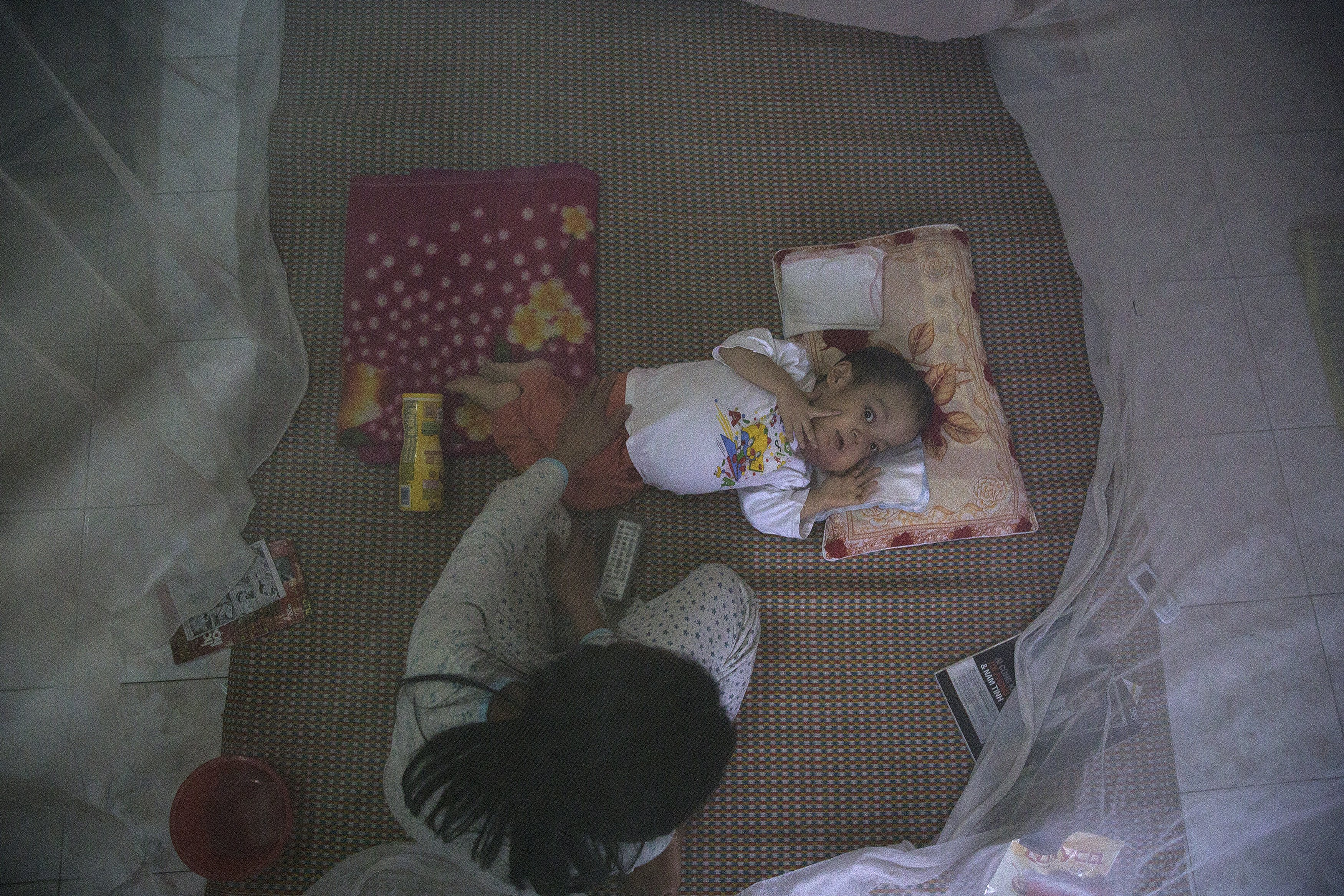 7-year-old Nguyen Van Tuan Tu, who suffers from serious health problems, is looked after by a family member under a mosquito net in their house near the airport in Danang, in central Vietnam April 12, 2015. When Nguyen Van Tuan Tu's father started working at Danang International Airport in 1997, he was not aware of the health risks associated with Agent Orange and he collected fish and snails from a contaminated lake nearby for the family to eat. His first child to be born after he started working at the airport was born in 2000 and died in 2007. Nguyen Van Tuan Tu was born in 2008 with same symptoms as his late sister and doctors and parents believe their health problems are linked to the effects of Agent Orange. The couple have one healthy daughter who was born in 1995, before they started working at the airport, and she is now a university student.