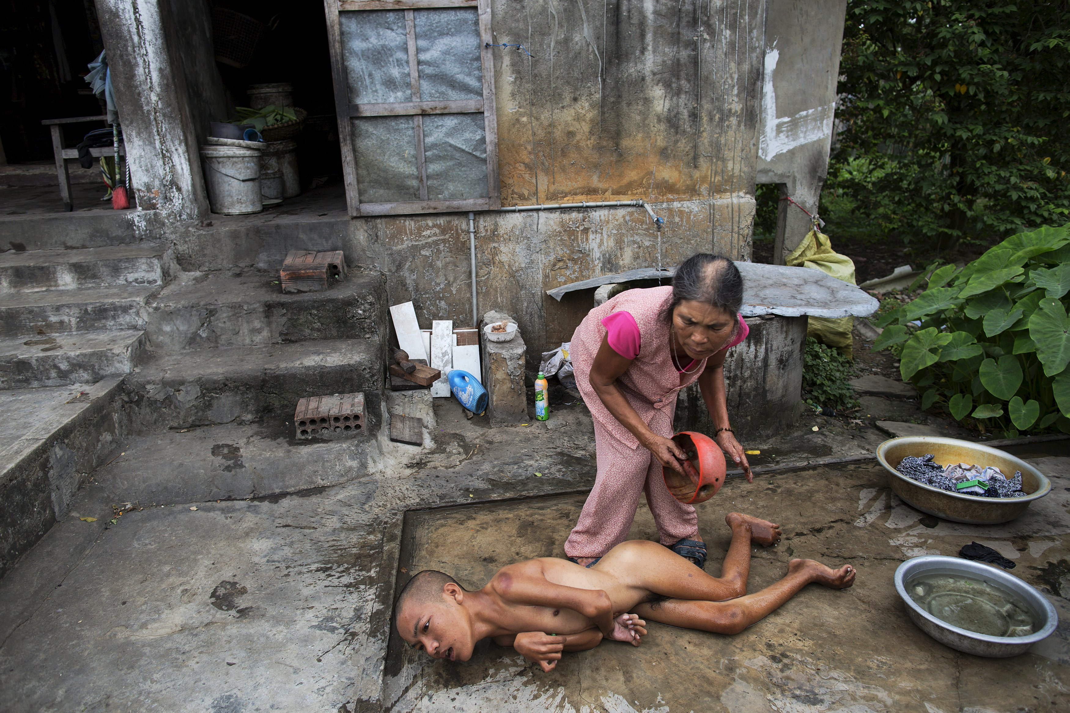 Tang Thi Thang baths her disabled son Doan Van Quy outside their family home in Truc Ly, in Vietnam's Quang Binh Province April 11, 2015. Doan Van Quy's father, a soldier who served on 12.7 mm anti-aircraft guns during the Vietnam War, said he lived in several areas that were contaminated by Agent Orange. Two of his sons were born with serious health problems and the family and local health officials link their illnesses to their father's exposure to Agent Orange.