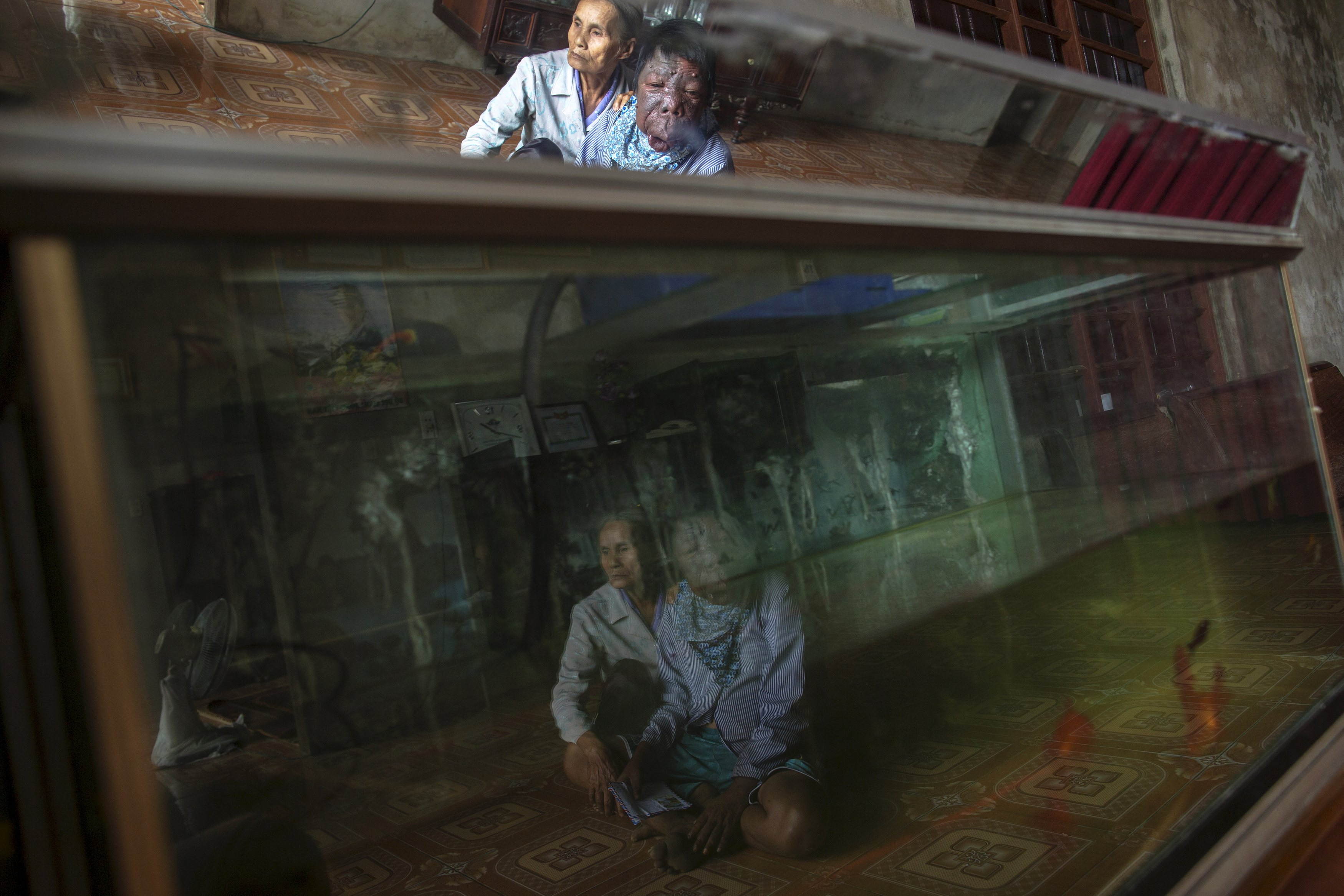 Dang Thi Quang and her son Nguyen Van Binh are reflected in an aquarium in their home in Vietnam's Quang Binh province April 11, 2015. Nguyen Van Binh's father, a soldier who served in the Vietnamese army's transportation unit in the North, travelled and spent time in areas known as hotspots for Agent Orange contamination.