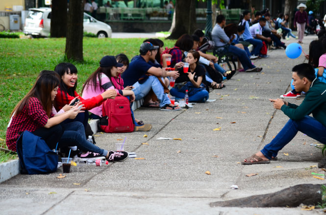 Groups of young people seek relief from the intolerable heat under the canopy at a Ho Chi Minh City park.