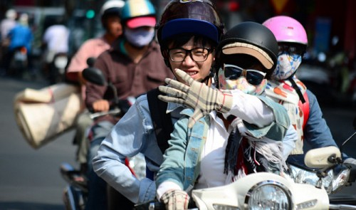 A woman is armed with sunglasses, a mask, hat, scarf and gloves while driving in the blazing heat.