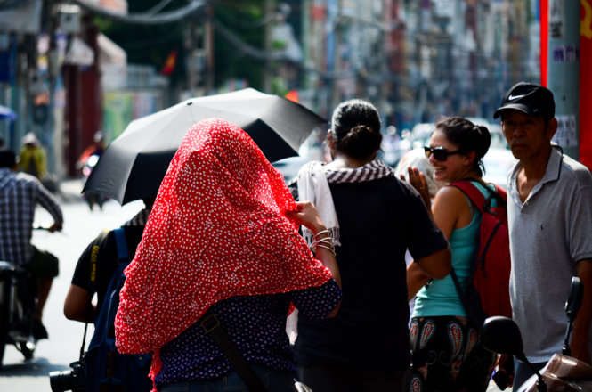 Some foreigners don scarves and carry umbrellas while walking under the sun.