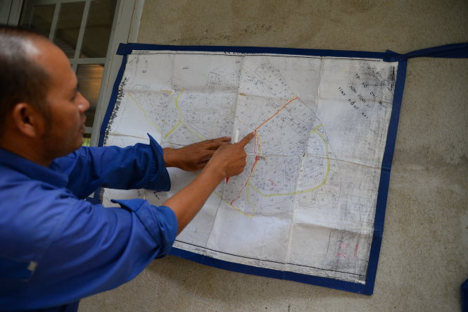 "H., a resident, points at his ""evaporated"" land plot on a map."