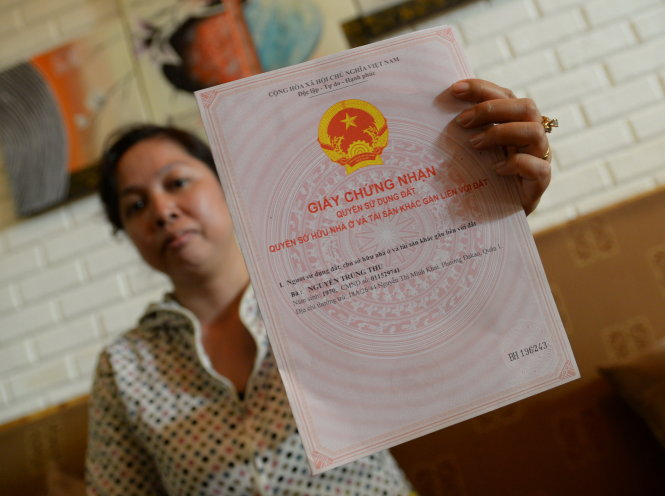 Nguyen Trung Thu, a local land owner who has lost over 1,000 square meters of land to illegal sand exploiters, shows her land use right certificate.