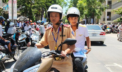 A traffic police officer takes a student to his exam venue in the central city of Da Nang. The activity is part of local traffic police's program to help students during the exam.