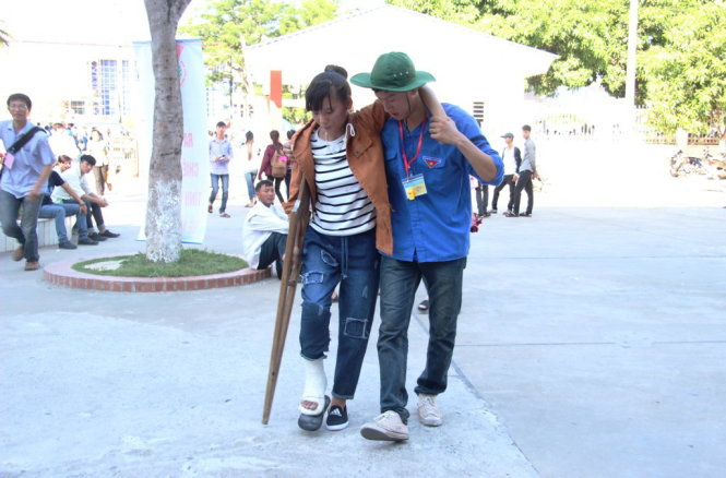 A volunteer helps Phan Thi Tam, a student from Mai Thuc Loan High School in the northern province of Ha Tinh's Loc Ha District, walks with a crutch to her exam venue for registration in Vinh City in Nghe An Province on June 30, 2015. Tam said she broke her right leg in a road accident a month ago. She added that she was about to give up because she thought she could not come to the exam venue, but thanks to the support from family and friends, she is determined to pass this important exam.