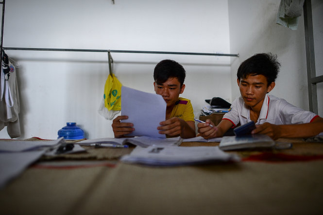 Nguyen Van Dat and Dinh Bat Hao from southern Binh Phuoc Province review their lessons the night before the exam in the Industrial University of Ho Chi Minh City's boarding house, where they stay free-of-charge.