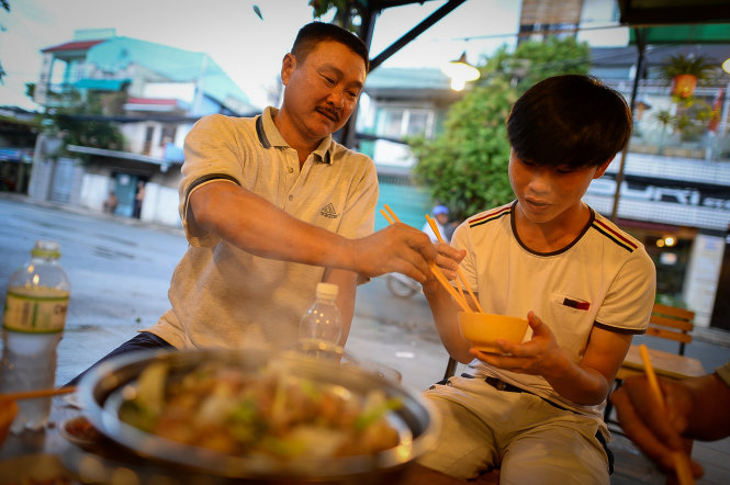 Ly Thanh Huy from Binh Phuoc Province treats his son to a good dinner one day before the exam at a goat meat eatery on Le Loi Street in Go Vap District, Ho Chi Minh City.