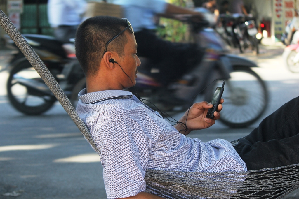Nguyen Danh Dao, from Quang Loc Commune, Can Loc District in the north-central province of Ha Tinh, listens to the radio while waiting for his son to take the exam on July 1, 2015.