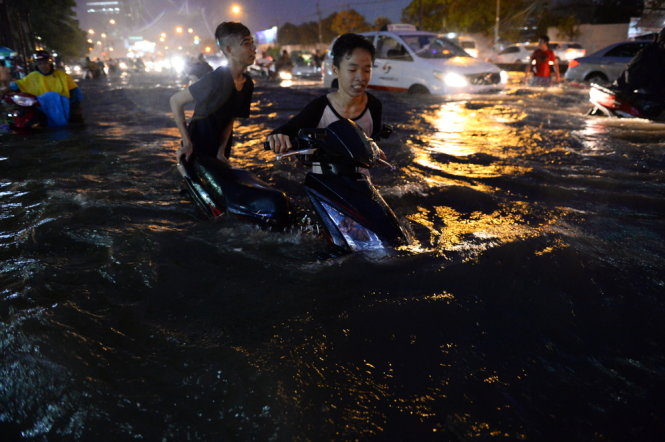 Two young people are seen trying to push their motorbike through a seriously submerged section of Nguyen Huu Canh Street in Binh Thanh District, Ho Chi Minh City on the evening of September 15, 2015. Photo