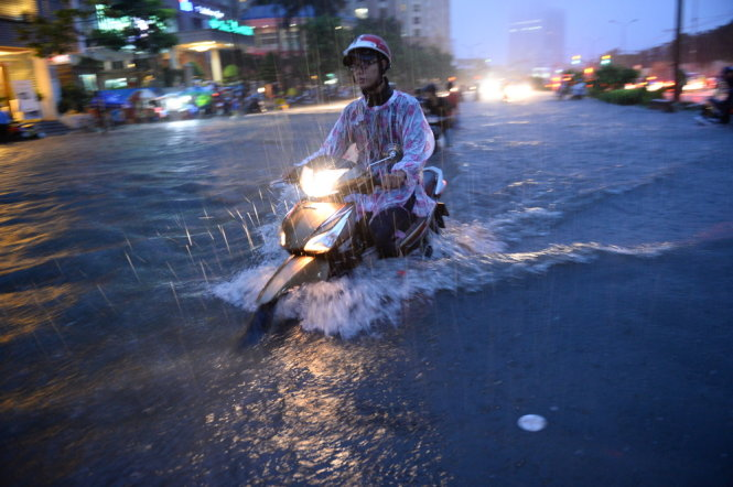 A driver tries to get through a heavily flooded section of  Nguyen Huu Canh Street.