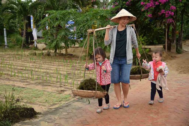 Stirling's mother carries the ganh, bamboo yokes hung with baskets at each end used to carry vegetables around, while Stirling and her younger brother walk alongside.