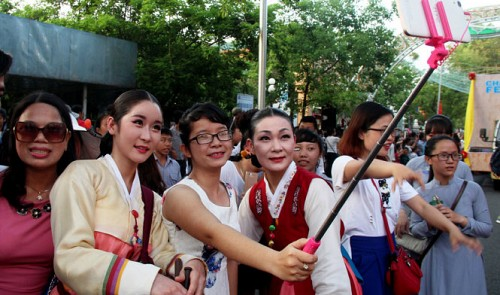 """South Korean artists take photos with Vietnamese audiences at the """"Heritage and Cultural Colors"""" street festival during the 2016 Hue Festival in Hue, located in central Vietnam, on May 1, 2016"""