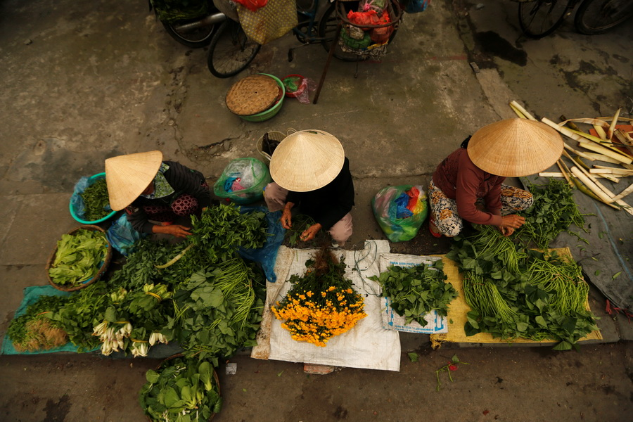 Women wearing traditional hats, known as a non la, sit in a market in Hoi An, Vietnam April 5, 2016.