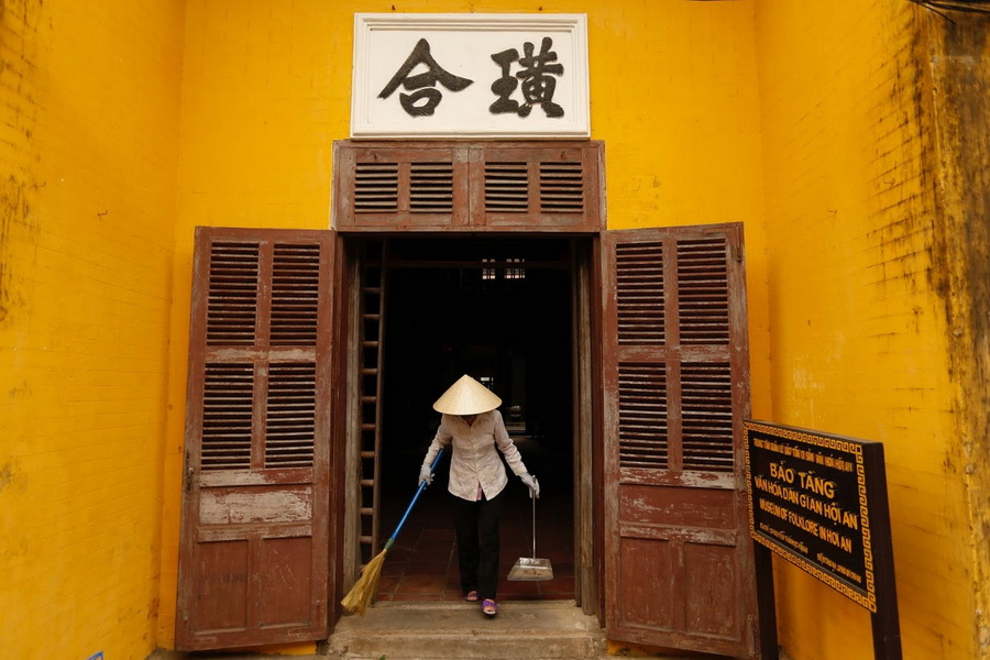 A woman wear a non la while cleaning the Museum of Folklore in Hoi An.