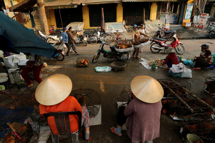 Women wearing traditional hats, known as a non la, sit in a market in Hoi An, Vietnam April 7, 2016.