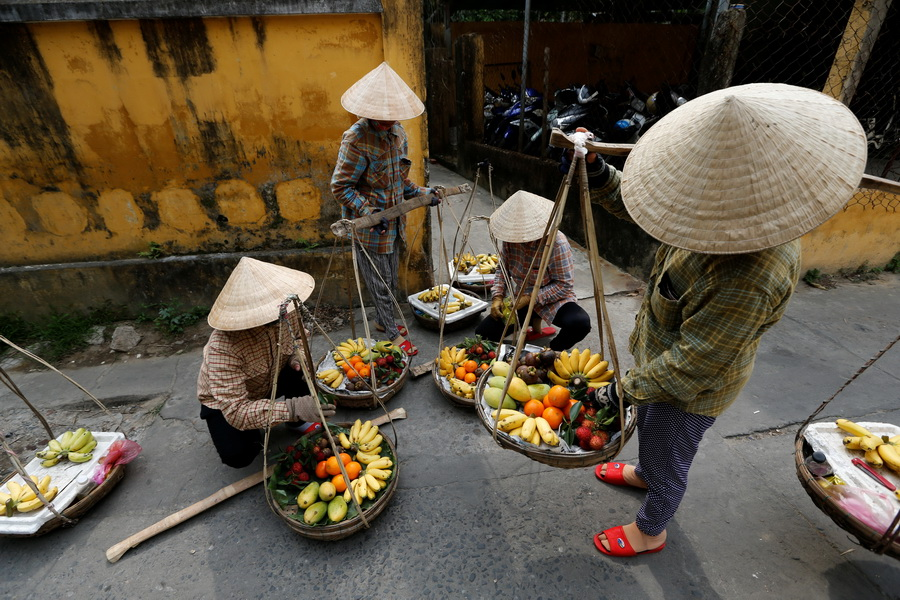 Women wearing traditional hats, known as non la, sell fruits in Hoi An, Vietnam April 4, 2016.