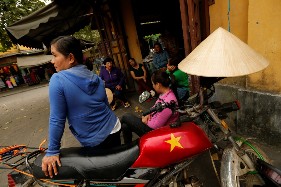 A woman sits on a motorcycle outside a market in Hoi An, Vietnam April 4, 2016.