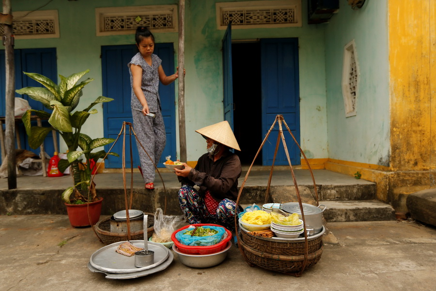 A woman wearing a traditional hat, known as a non la, sells food for breakfast in Hoi An, Vietnam April 5, 2016.