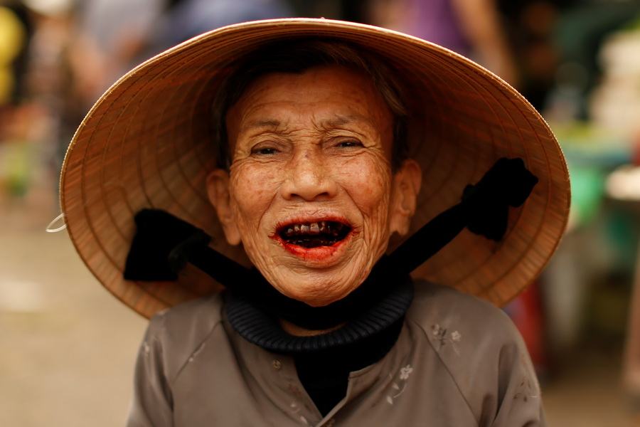A woman wearing a traditional hat, known as a non la, poses for a portrait at a market in Hoi An, Vietnam April 5, 2016.