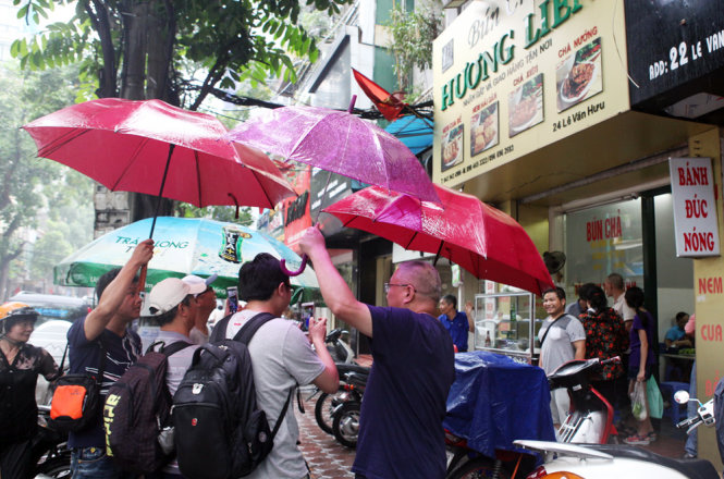 A number of dinners walk to Huong Lien Outlet with umbrellas due to the rain