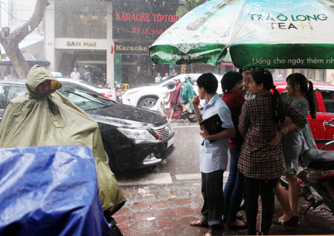 Diners patiently wait in front of the outlet despite the heavy rain.