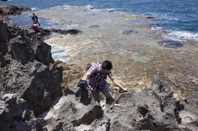 Tourists climb over sharp stones.