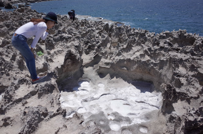 A tourist watches salt crystallized in a rut