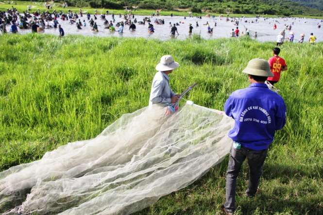 Three people are seen carrying their fishing nets to the swamp.