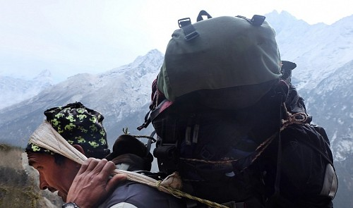 A porter carries a large load of luggage on the Himalayas.