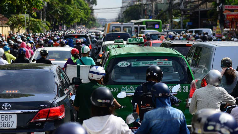 Motorbikes zigzag between cars and taxis.