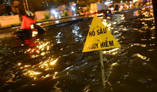 A sign warning travelers of a deep hole is seen being covered in floodwaters.